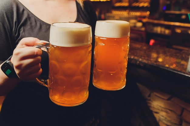 Waiter serving glasses of cold beer on the tray. Premium Photo