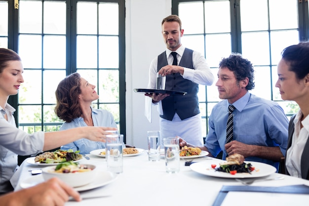 Waiter serving water to business people Premium Photo