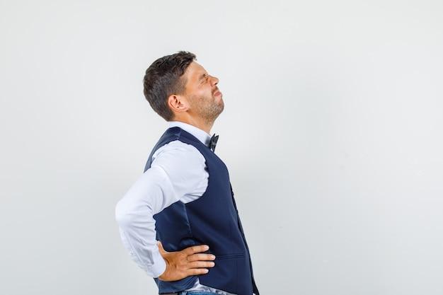 Cameriere in camicia, gilet, jeans che soffrono di mal di schiena e sembra malato. Foto Gratuite