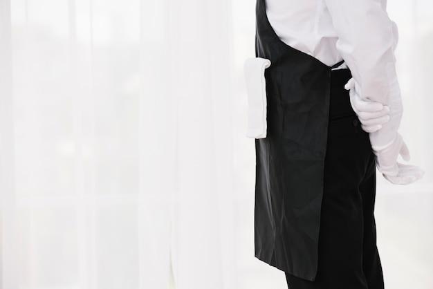 Официант стоит с руками на спине Бесплатные Фотографии