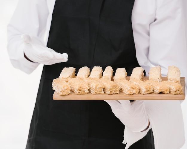 Waiter in uniform presenting desert Free Photo