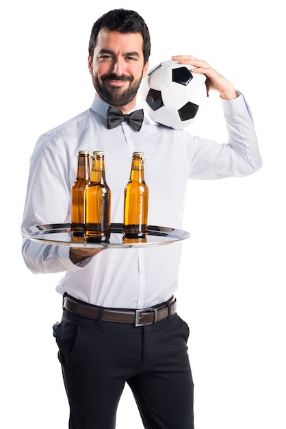 Waiter with beer bottles on the tray holding a soccer ball Free Photo