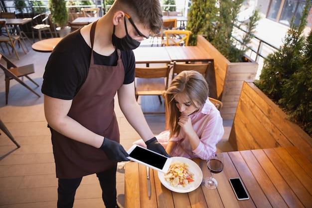 Официант работает в ресторане в медицинской маске, перчатках во время пандемии коронавируса Бесплатные Фотографии