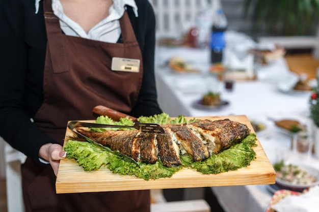 Waitress in a black uniform holding a wooden plate with baked fish in a restaurant Premium Photo