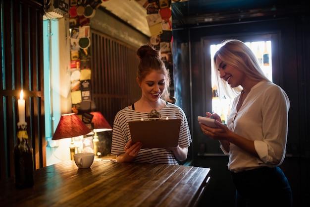 Официантка обсуждает меню с заказчиком Бесплатные Фотографии