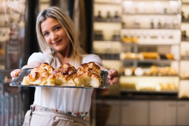 Waitress offering croissant tray Free Photo