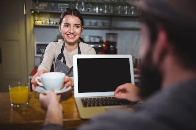 Waitress serving a cup of coffee to customer Free Photo