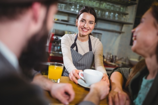Waitress serving a cup of coffee to customers Free Photo