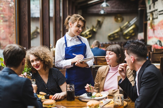 Waitress taking orders from people in restaurant Free Photo