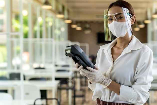 Waitress with face mask hold credit card reader. Premium Photo