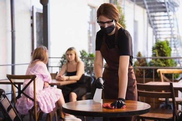La cameriera lavora in un ristorante con una mascherina medica, guanti durante la pandemia di coronavirus Foto Gratuite