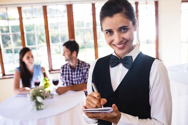 Waitress writing order on notepad in restaurant Premium Photo