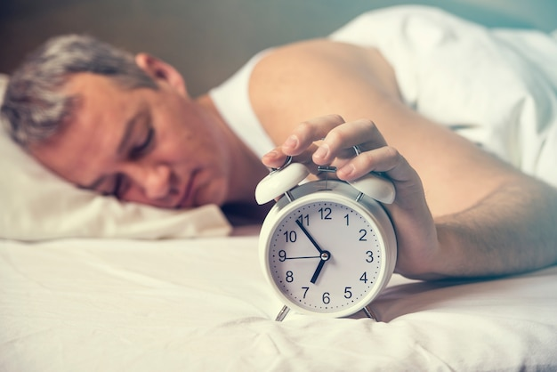 Waked up. hand turns off the alarm clock waking up at morning . soft skin tone . exhausted man being awakened by an alarm clock in his bedroom Free Photo