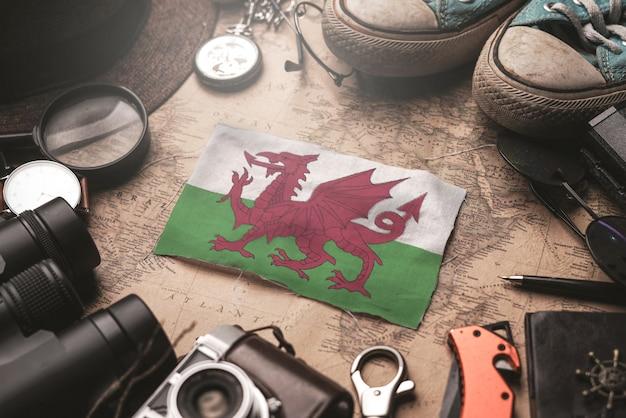 Флаг уэльса между аксессуарами путешественника на старой винтажной карте. концепция туристического направления. Premium Фотографии