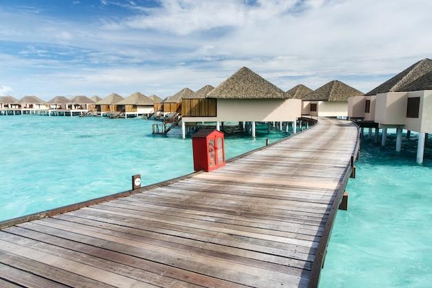 Walk way to water villa on crystal clear water at island Premium Photo