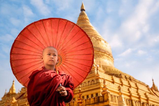 シュエズィーゴンパヤの黄金の仏塔でウンベラとビルマの僧walkの散歩 Premium写真