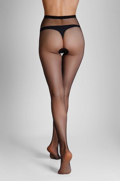 Walking away long slim female legs in black fishnet tights. back view. Premium Photo
