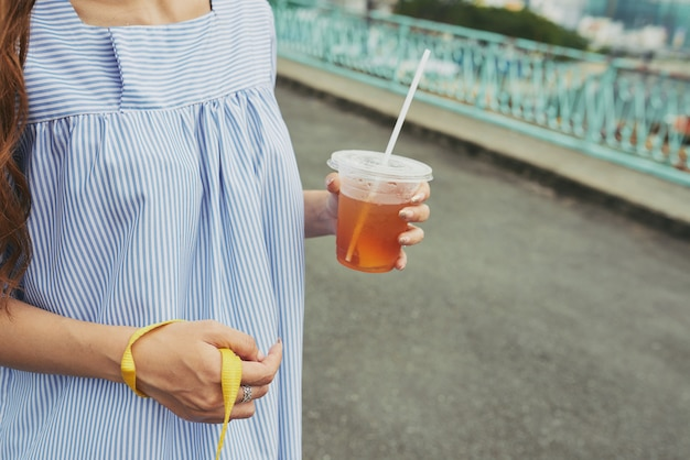 Walking with iced tea in hands Free Photo