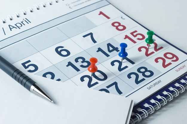 Wall calendar and pen, important days are marked with knops Premium Photo