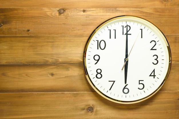 Wall clock on the wooden wall Premium Photo