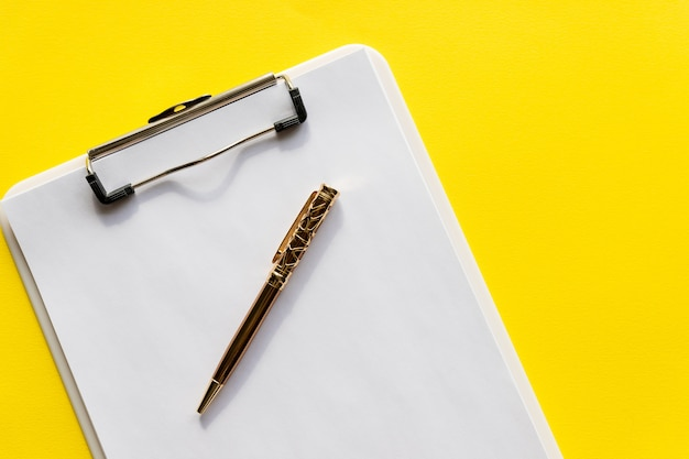 Буфер обмена с чистого листа. черная доска сзажимом для бумаги с белой пустой пустой бумагой с ручкой на ей, на желтом космосе wall.copy для текста. минималистичный дизайн, концепция рабочего пространства Premium Фотографии