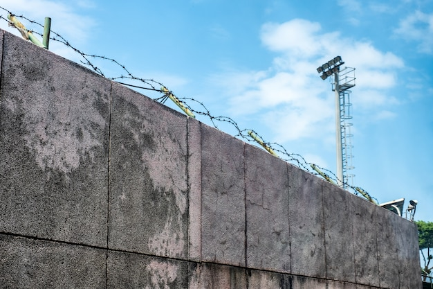Wall stone with coils barbed wire and security camera Premium Photo