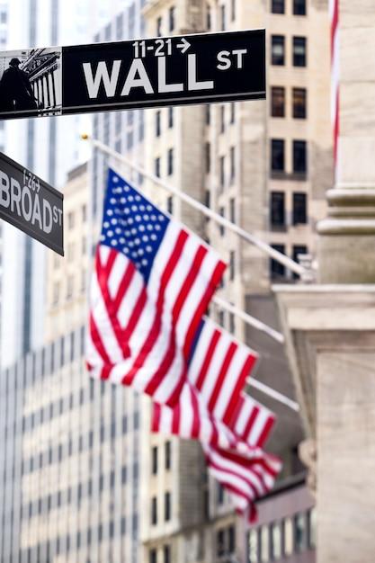 Знак уолл-стрит в нью-йорке с фоном нью-йоркской фондовой биржи Бесплатные Фотографии