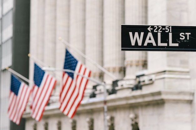 Wall street sign post with american national flags in background. Premium Photo