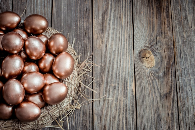 Wall with golden easter eggs on wooden wall. Free Photo