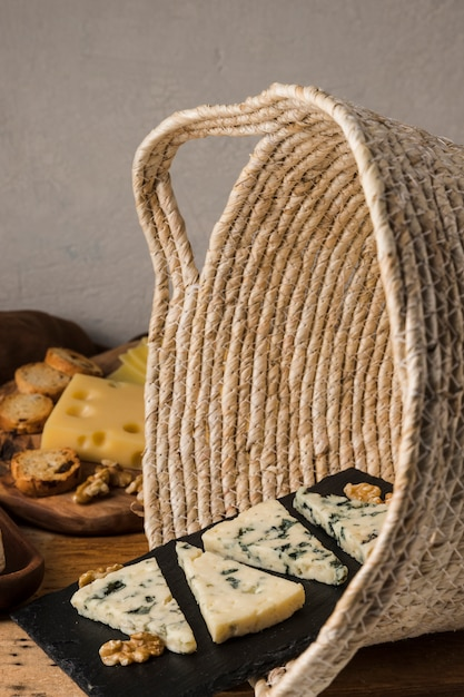 Walnut and blue cheese on black slate in wicker basket Free Photo