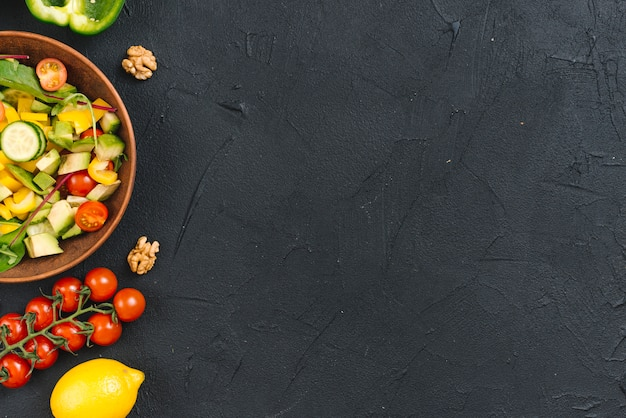 Walnut and fresh vegetable salad on black concrete backdrop Free Photo