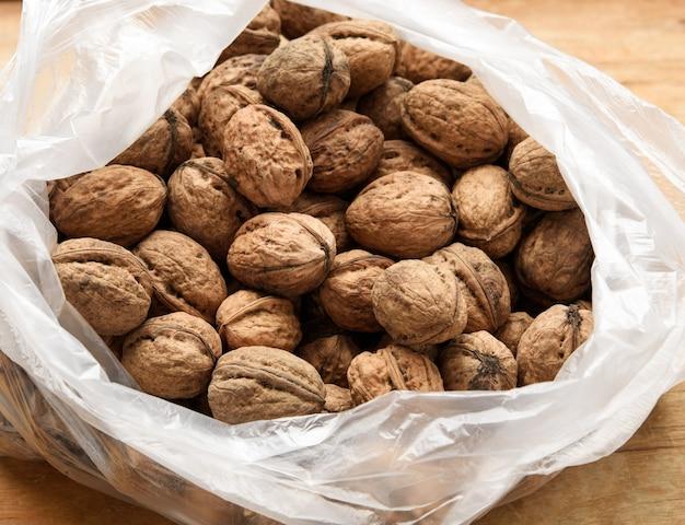 Грецкий орех в полиэтиленовом пакете на деревянном столе, вид сверху Premium Фотографии