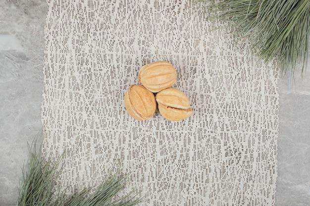 枝のある黄麻布にくるみの形をしたクッキー。高品質の写真 無料写真