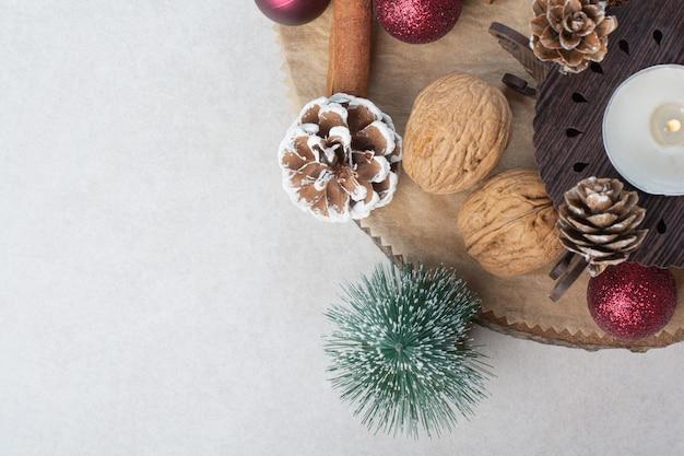 木の板に松ぼっくりとクリスマスボールとクルミ。高品質の写真 無料写真