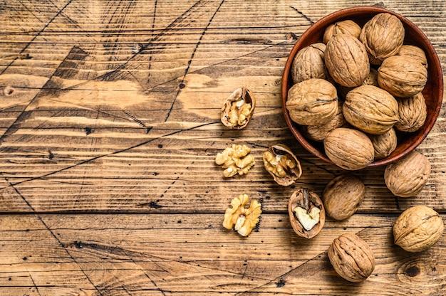 Грецкие орехи в деревянной тарелке и ядра грецких орехов Premium Фотографии