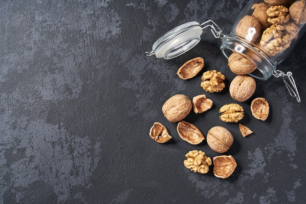 Walnuts in an open glass jar on black table, close-up. Premium Photo