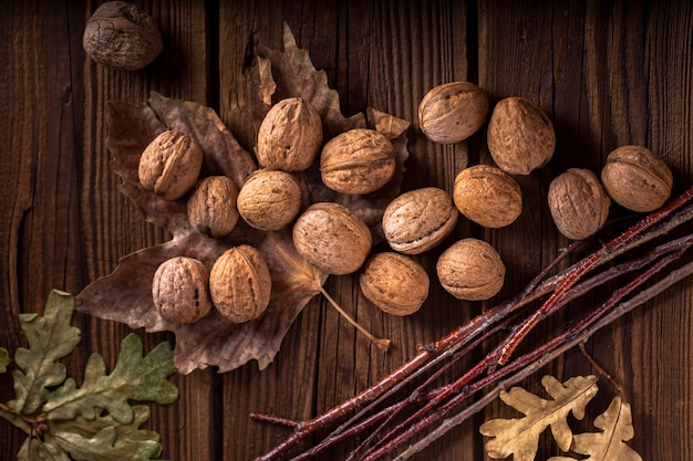 Walnuts on wooden table with leaves Free Photo