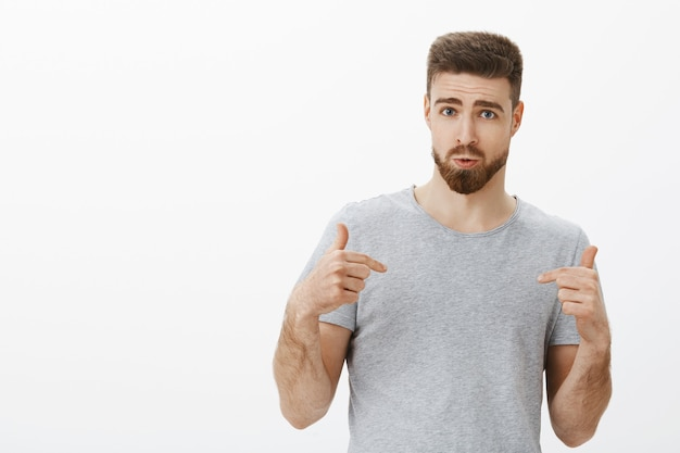 こんな完璧な体になりたい。スタイリッシュなひげと髪型が自分を指している自信のあるハンサムな男性が疑問を抱き、自信を持って体育館の訪問者に栄養プログラムを勧める 無料写真
