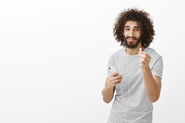 Хочу поделиться наушниками. дружелюбная симпатичная стройная мужская модель в полосатой футболке, тянет наушники к смартфону и держит в руке Бесплатные Фотографии