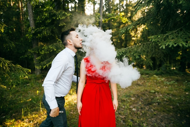 Мужской wape курильщик дует густое облако дыма к уху своей подруги в красном платье с забавным эмоциональным лицом. Premium Фотографии