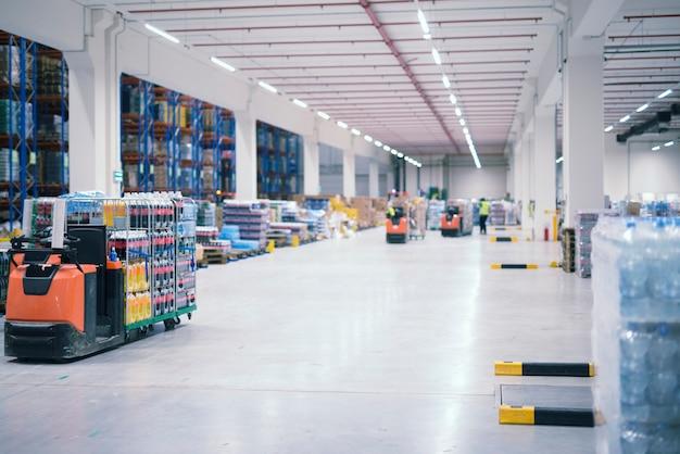 Интерьер промышленного здания склада с людьми и вилочными погрузчиками, обрабатывающими товары на складе Бесплатные Фотографии