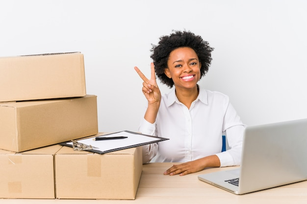 Warehouse manager sitting checking deliveries with laptop showing number two with fingers. Premium Photo