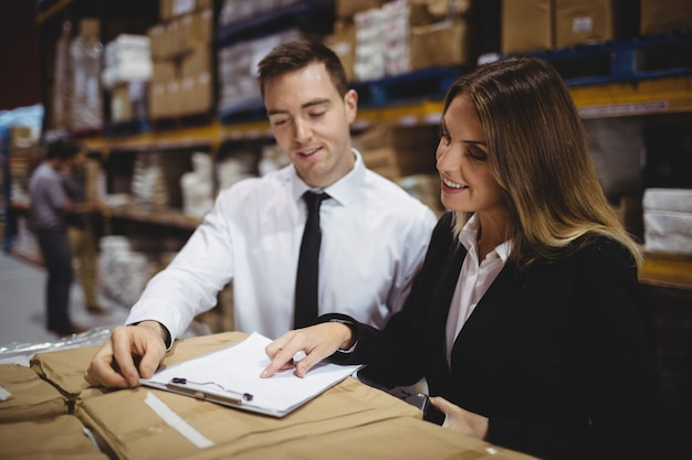 Warehouse managers looking at clipboard on boxes Premium Photo