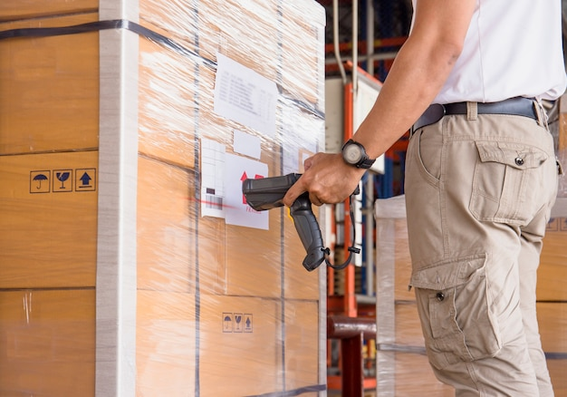 Warehouse worker are holding bar code scanner with scanning on the shipment pallet. Premium Photo