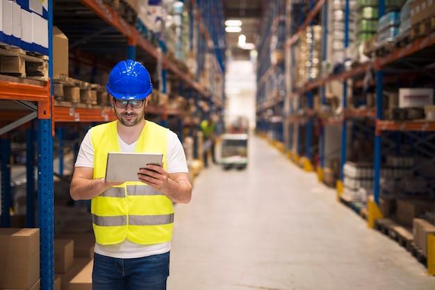 Работник склада проверяет инвентарь на своем планшете во время прогулки по большому складскому помещению с полками и упаковками на заднем плане Бесплатные Фотографии