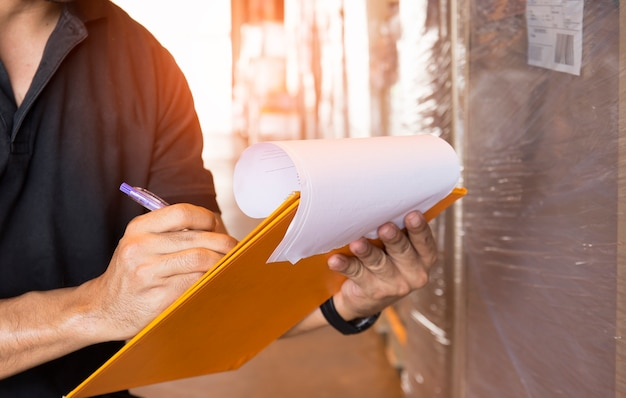 Warehouse worker hand holding clipboard with checking inventory of products Premium Photo