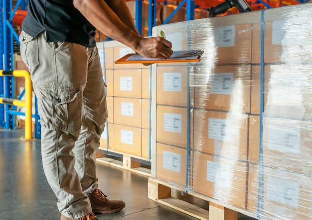 Warehouse worker holding clipboard is inventory cargo products at warehouse. Premium Photo