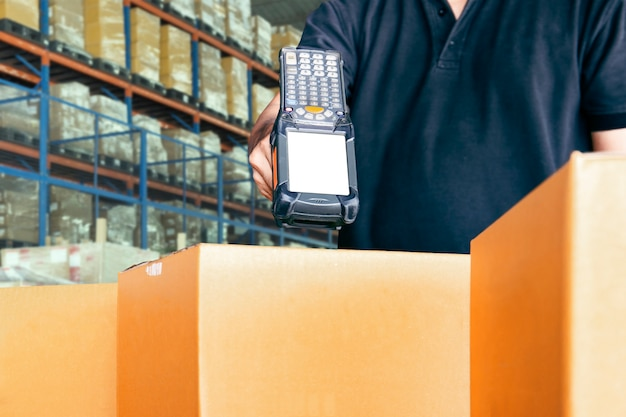 Warehouse worker is scanning bar code scanner with cardboard boxes. Premium Photo