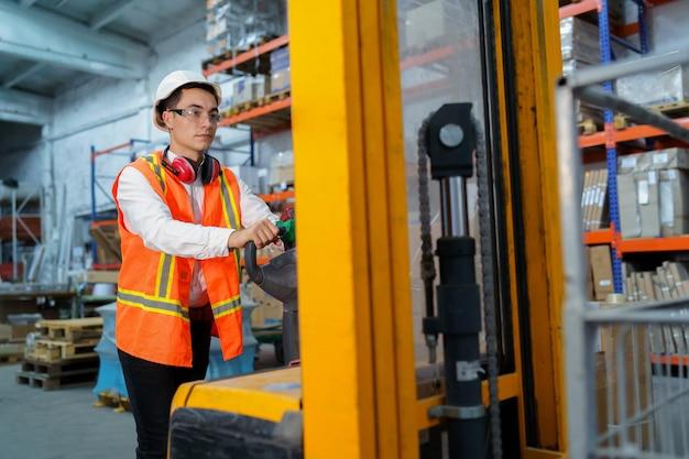 倉庫作業員はパレットローダーを操作します Premium写真