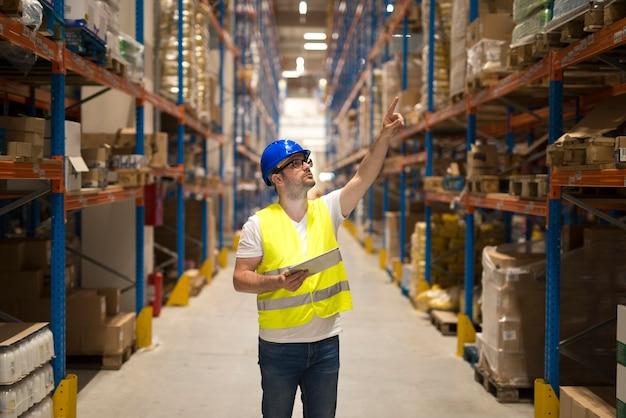 Addetto al magazzino in uniforme riflettente protettiva con elmetto protettivo che controlla l'inventario e conta il prodotto sullo scaffale in un'ampia area di stoccaggio Foto Gratuite